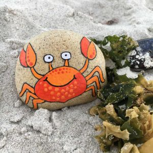 Crab painted on a rock next to some seaweed